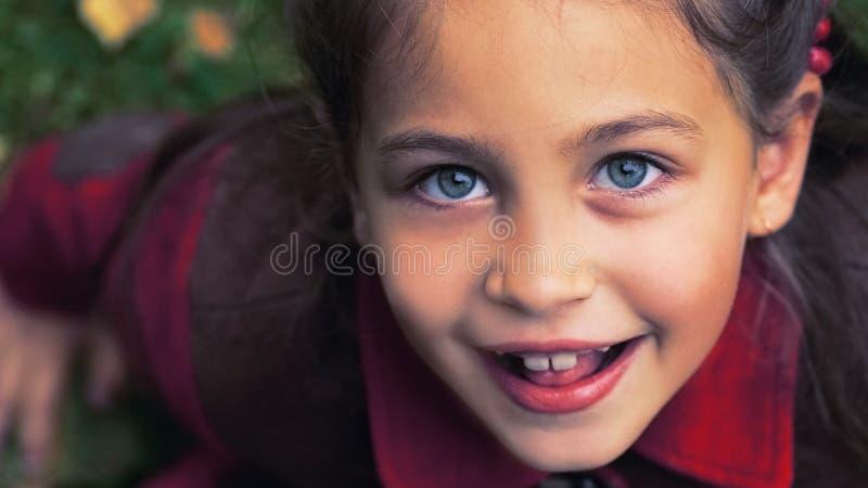 Ritratto adorabile sveglio della ragazza del bambino con le foglie di autunno sulla terra ai precedenti Bambino all'aperto in par immagine stock libera da diritti