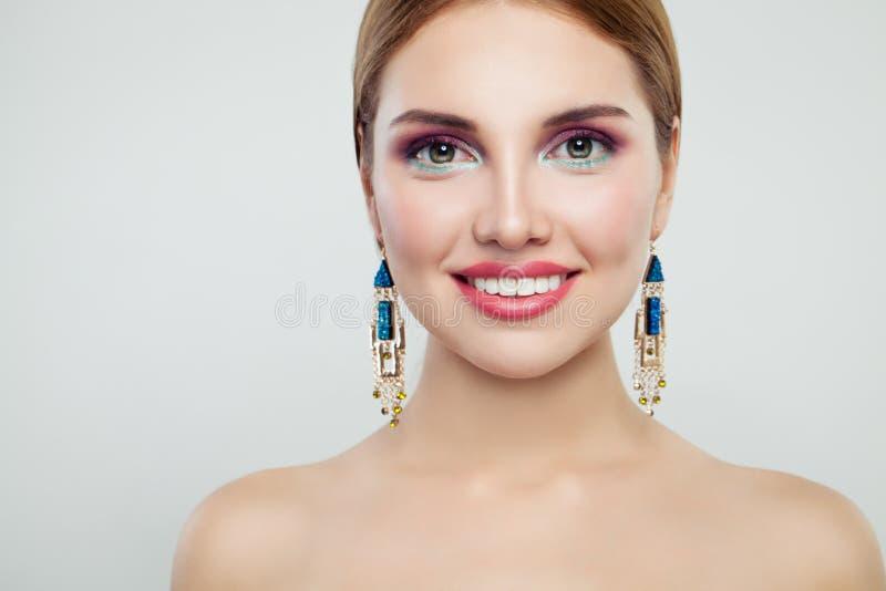 Ritratto affascinante di modo della donna Ragazza sveglia con gli orecchini variopinti dell'oro e di trucco immagini stock libere da diritti