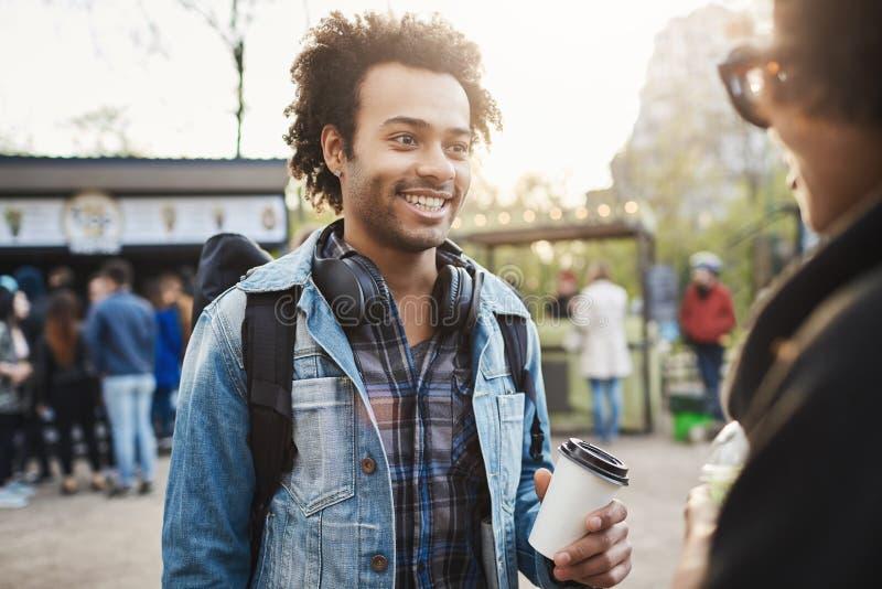 Ritratto all'aperto del maschio afroamericano ottimistico alla moda con l'acconciatura di afro e della setola che tiene tazza di  fotografie stock