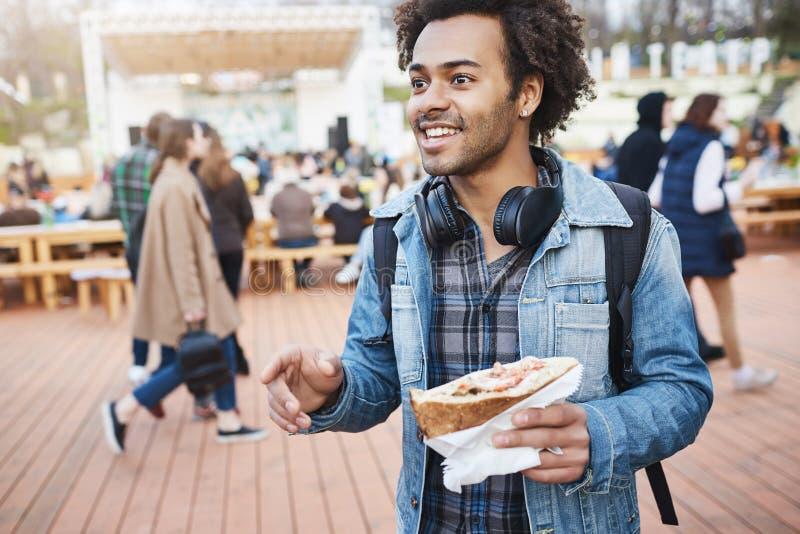 Ritratto all'aperto del panino afroamericano positivo della tenuta dello studente mentre gesturing e parlando con amico, camminan immagini stock libere da diritti