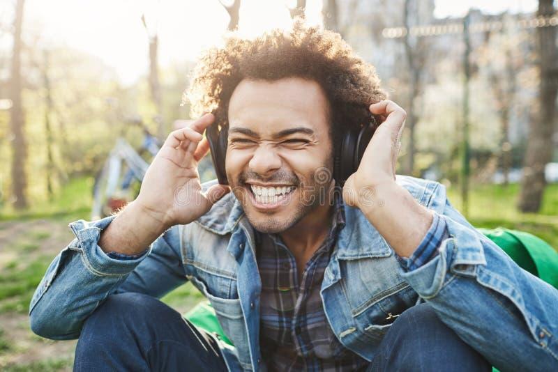 Ritratto all'aperto del primo piano dell'uomo africano bello con taglio di capelli di afro che si tiene per mano sulle cuffie men fotografia stock libera da diritti