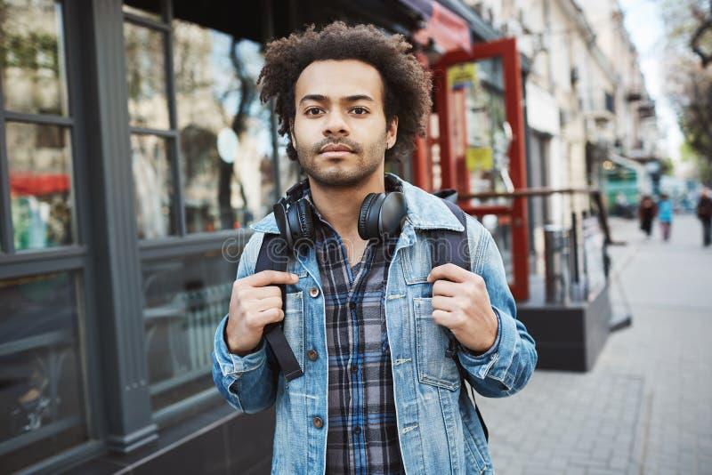 Ritratto all'aperto del viaggiatore dalla carnagione scura alla moda con l'acconciatura di afro che cammina sulla via Prove dell' fotografie stock libere da diritti