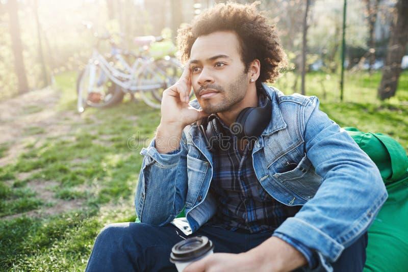Ritratto all'aperto dell'uomo africano alla moda che si siede nel parco con la tazza di caffè, tenente mano sul fronte e guardant fotografia stock