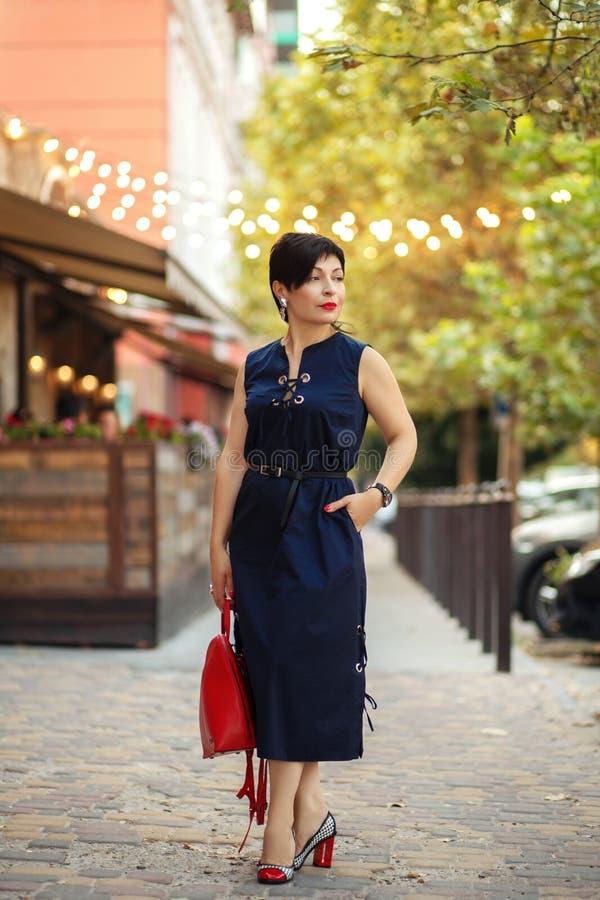 Ritratto all'aperto della donna castana della scorciatoia in vestito alla moda ed in borsa rossa, attrezzatura d'avanguardia di e fotografie stock libere da diritti