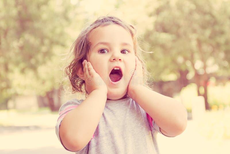 Ritratto all'aperto della ragazza sveglia sorpresa del bambino sul backgro naturale immagini stock libere da diritti