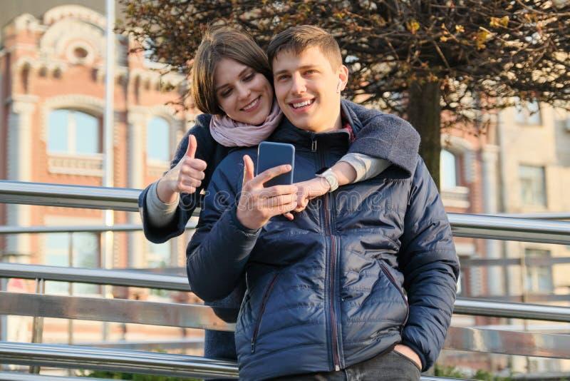 Ritratto all'aperto delle coppie che mostrano approvazione del segno di gesto Giovane e donna con lo smartphone in cuffie, ora do fotografia stock libera da diritti