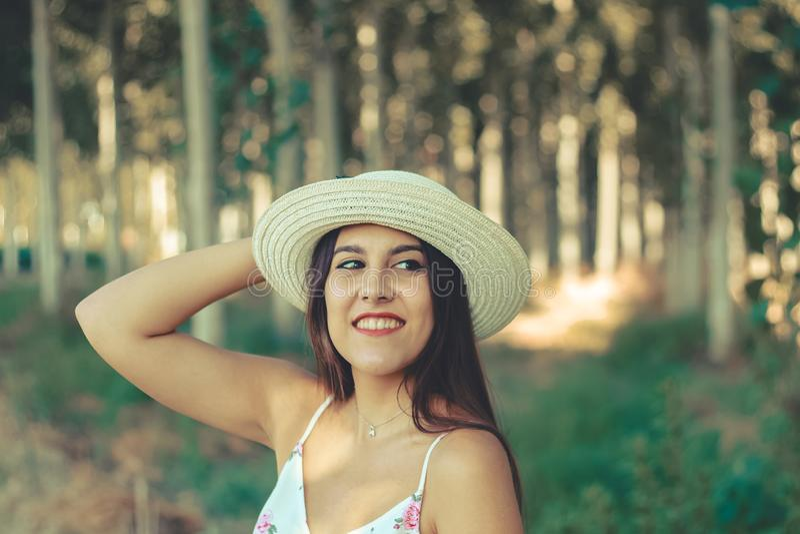 Ritratto all'aperto di bella ragazza castana sorridente che porta un cappello del sole fotografia stock