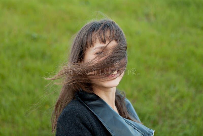 Ritratto all'aperto di bella ragazza che ride mentre il vento si muove fotografia stock