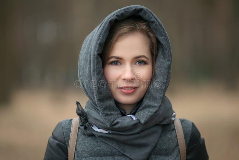 Ritratto all'aperto di bello cappotto d'uso sorridente della giovane donna con il cappuccio Effetto tonificato immagine stock libera da diritti