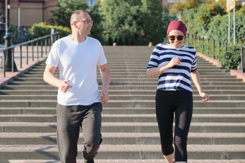 Ritratto all'aperto di eseguire le coppie mature Uomo e una donna di 40 anni che eseguono sulle scale fotografia stock libera da diritti