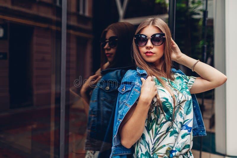 Ritratto all'aperto di giovane bella donna alla moda che indossa gli accessori alla moda Attrezzatura moderna di estate immagini stock