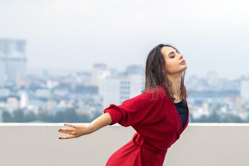 Ritratto all'aperto di giovane bella donna che balla sul tetto fotografia stock