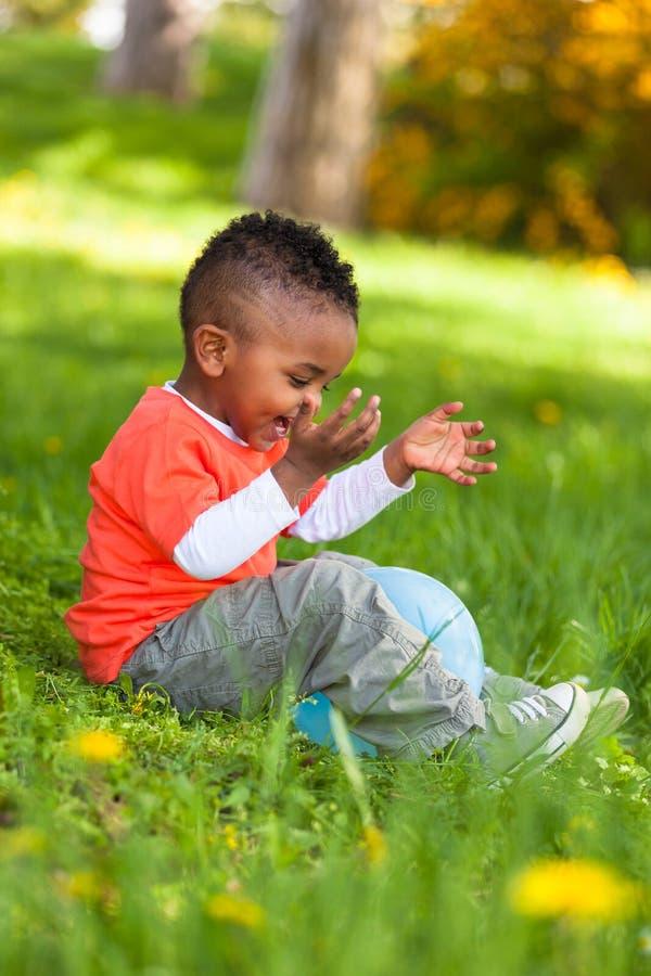 Ritratto all'aperto di giovane piccolo ragazzo nero sveglio che gioca con immagini stock libere da diritti