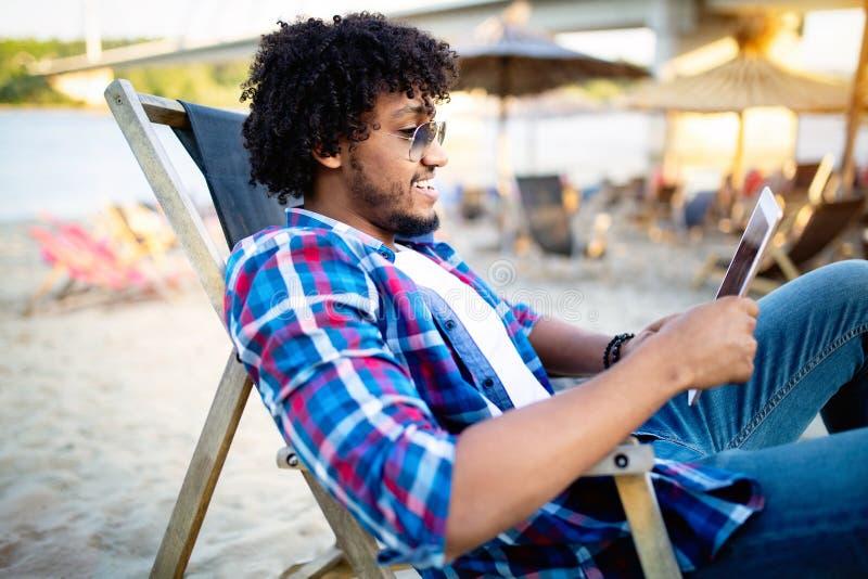 Ritratto all'aperto di giovane uomo africano felice facendo uso del computer della compressa fotografie stock libere da diritti