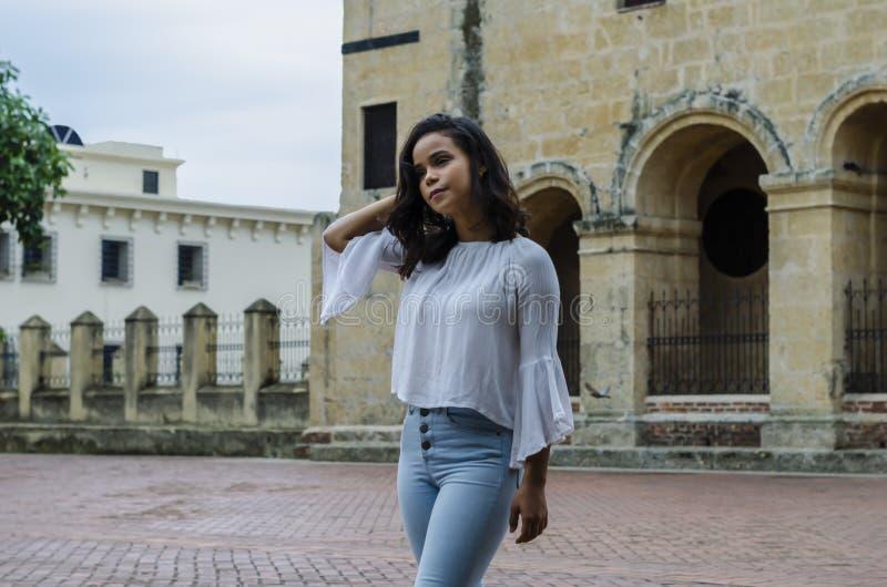 Ritratto all'aperto di giovani bei anni delle ragazze 9 - 25 che posano in via blusa bianca d'uso e jeans e sapatillas stretti immagine stock