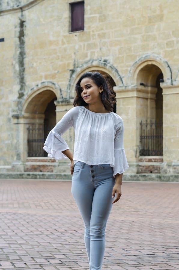 Ritratto all'aperto di giovani bei anni delle ragazze 9 - 25 che posano in via blusa bianca d'uso e jeans e sapatillas stretti fotografie stock
