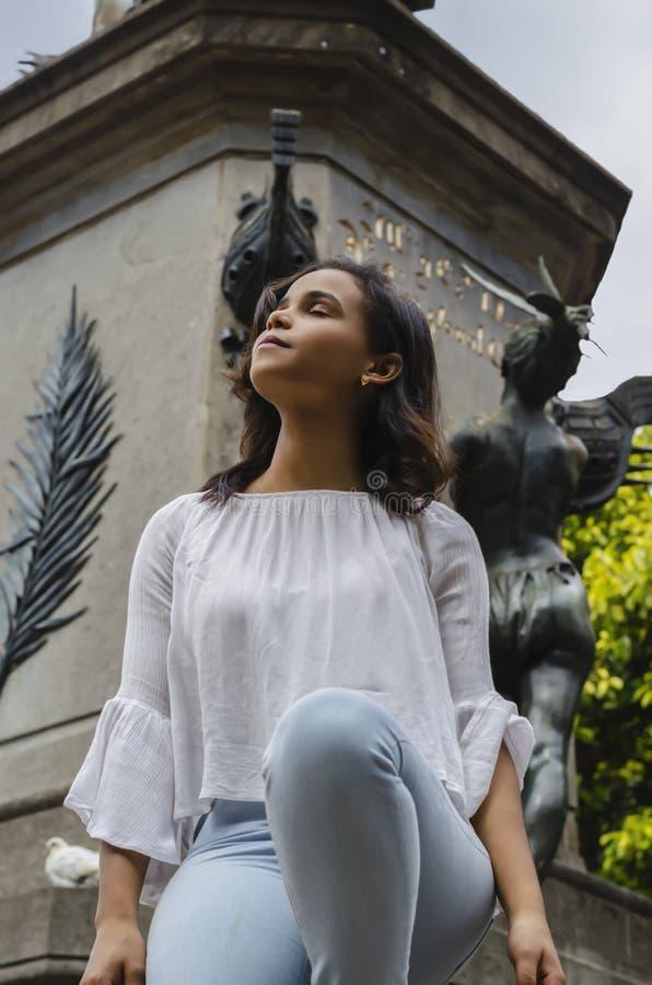 Ritratto all'aperto di giovani bei anni delle ragazze 9 - 25 che posano in via blusa bianca d'uso e jeans e sapatillas stretti immagine stock libera da diritti