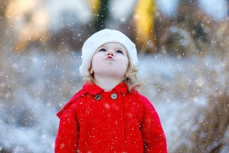 Ritratto all'aperto di inverno di poca ragazza sveglia del bambino in cappotto rosso e barret bianco del cappello di modo Bambino fotografia stock libera da diritti