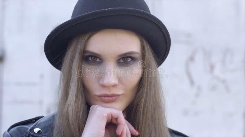 Ritratto all'aperto di modo della giovane donna alla moda divertendosi, fronte emozionale, ridere, esaminante macchina fotografic fotografia stock