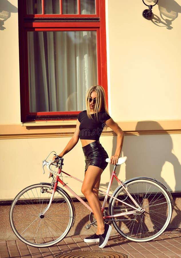 Ritratto all'aperto di modo di bella bionda con la bici fotografia stock libera da diritti