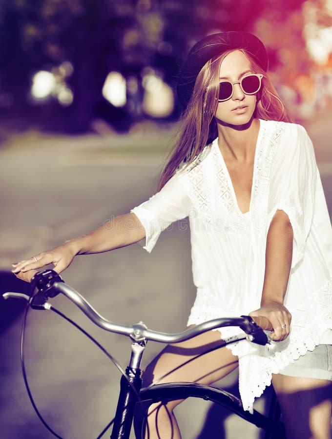 Ritratto all'aperto di modo di bella donna su una bicicletta immagine stock libera da diritti