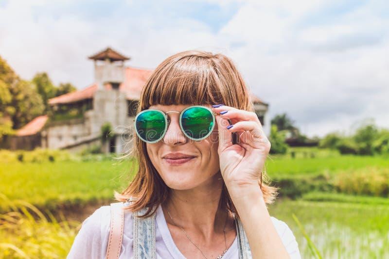 Ritratto all'aperto di modo di giovane bella signora in occhiali da sole, concetto di estate Giacimento del riso su un fondo trop fotografia stock