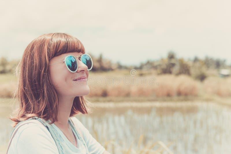 Ritratto all'aperto di modo di giovane bella signora in occhiali da sole, concetto di estate Giacimento del riso su un fondo trop fotografia stock libera da diritti