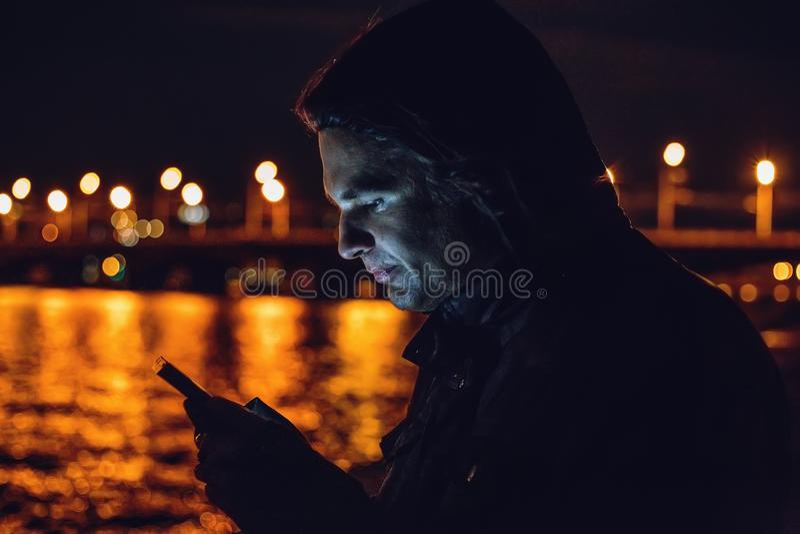 Ritratto all'aperto di notte del giovane che per mezzo del telefono cellulare fotografie stock