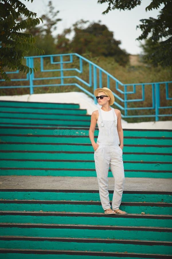 Ritratto all'aperto di stile di vita di estate della donna alla moda bionda graziosa in cappello di paglia fotografia stock