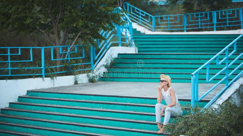 Ritratto all'aperto di stile di vita di estate della donna alla moda bionda graziosa in cappello di paglia immagine stock libera da diritti
