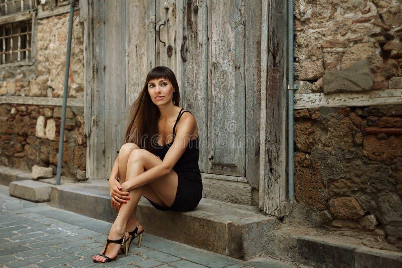 Ritratto all'aperto di stile di vita della ragazza graziosa, durante in vestito nero su fondo urbano Immagine tonificata colore c immagine stock