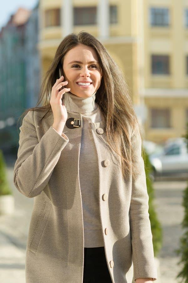 Ritratto all'aperto di una giovane donna felice sorridente con lo smartphone, fondo della via della città, giorno soleggiato di a fotografia stock