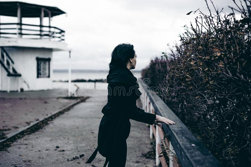 Ritratto alla moda di giovane donna castana in vestiti neri, jeans maglietta, cappotto ed occhiali da sole, in un umore triste di fotografia stock