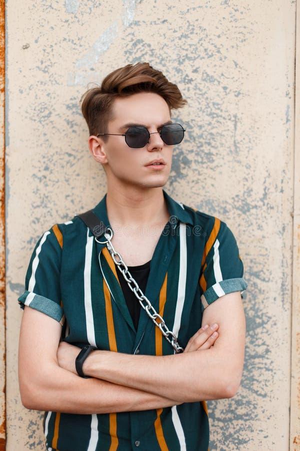 Ritratto alla moda di un giovane bello con gli occhiali da sole immagine stock libera da diritti