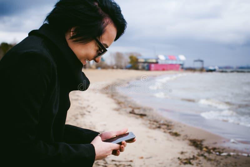 Ritratto alla moda emozionale di giovane donna castana in vestiti neri, jeans maglietta, cappotto ed occhiali da sole, in uno sti immagini stock libere da diritti