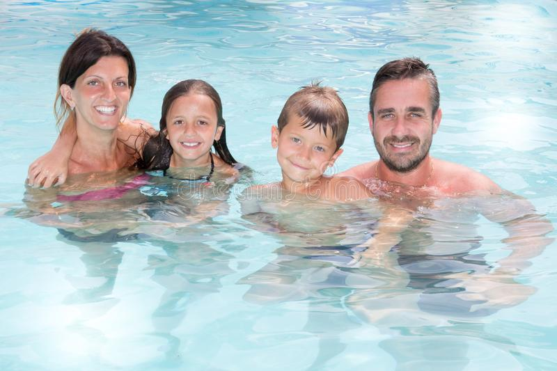 Ritratto allegro della famiglia nella piscina nelle vacanze estive immagine stock