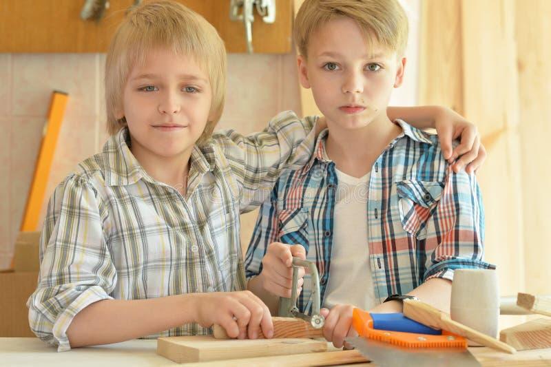 Ritratto alto vicino dei ragazzini svegli che lavorano con il legno in officina immagine stock