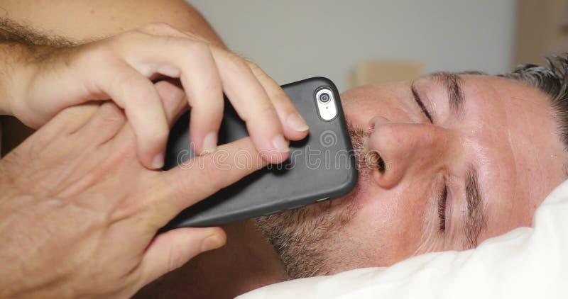 Ritratto alto vicino del fronte di giovane uomo attraente e felice che si trova sul letto facendo uso del telefono cellulare che  fotografia stock