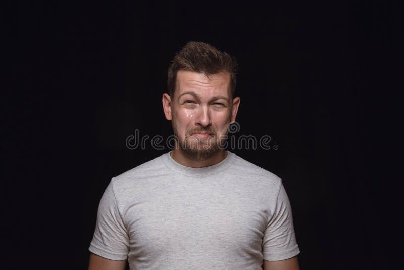 Ritratto alto vicino del giovane isolato sul fondo nero dello studio fotografie stock