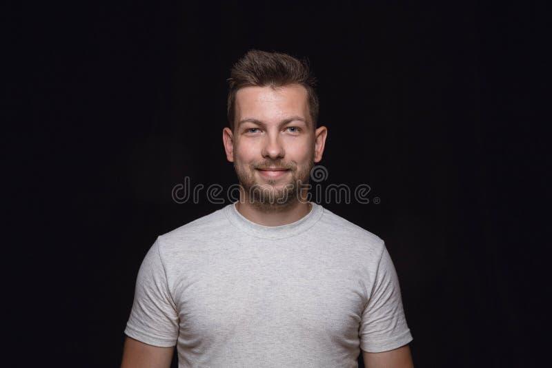 Ritratto alto vicino del giovane isolato sul fondo nero dello studio fotografia stock libera da diritti
