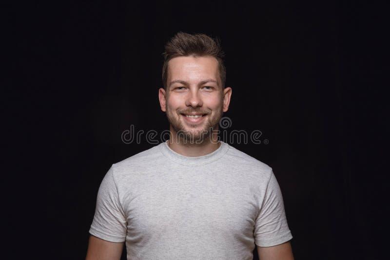 Ritratto alto vicino del giovane isolato sul fondo nero dello studio fotografia stock