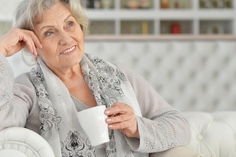 Ritratto alto vicino del tè bevente della donna senior mentre sedendosi sul sofà a casa fotografia stock