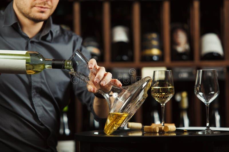 Ritratto alto vicino del vino bianco di versamento del sommelier caucasico in decantatore fotografie stock libere da diritti