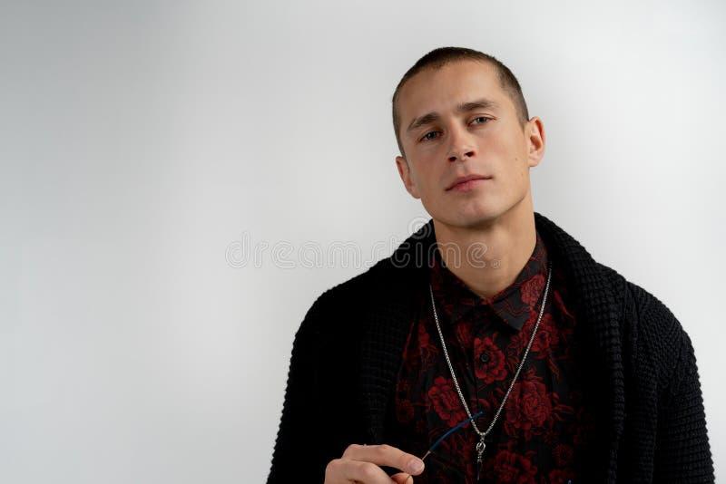 Ritratto alto vicino dell'uomo serio bello dell'aspetto moderno con breve taglio di capelli in maglione nero isolato su grigio immagini stock