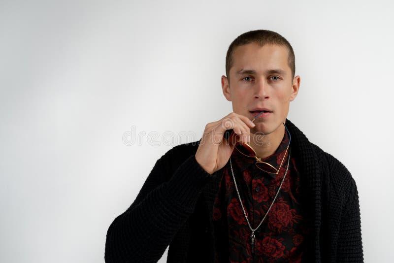 Ritratto alto vicino dell'uomo serio bello dell'aspetto moderno con breve taglio di capelli in maglione nero isolato su grigio fotografia stock libera da diritti