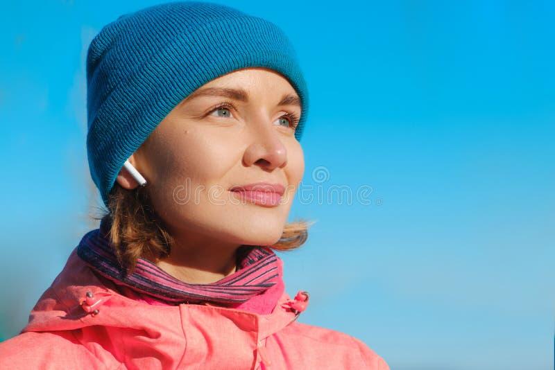 Ritratto alto vicino della donna sicura alla spiaggia che ascolta la musica in cuffie fotografia stock