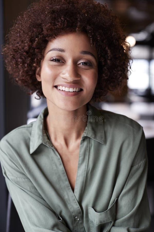 Ritratto alto vicino della femmina nera millenaria creativa in un ufficio che sorride alla macchina fotografica fotografia stock libera da diritti