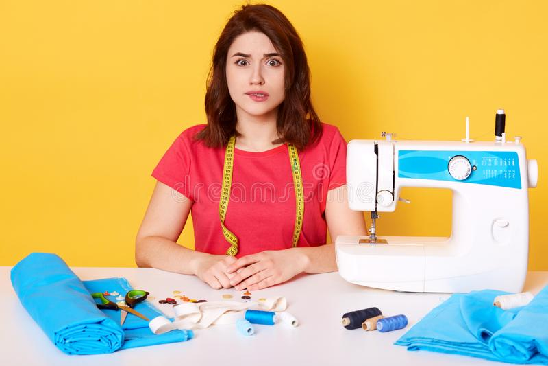 Ritratto alto vicino della fogna professionale della donna in maglietta rossa casuale all'atelier, esaminando direttamente la mac fotografia stock
