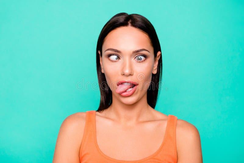 Ritratto alto vicino della foto dello sciocco di gioco funky divertente che la rende a fronti la sua ragazza che attacca lingua f immagine stock libera da diritti
