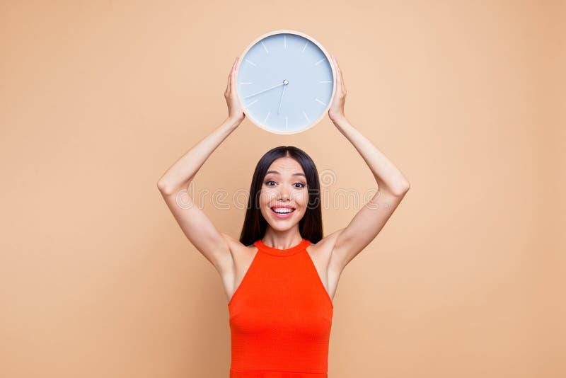 Ritratto alto vicino della foto di bella signora sicura graziosa che tiene grandi spese generali dell'orologio sulla copia beige  fotografie stock